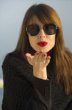 Red kiss. Beautiful elegant young woman wearing sunglasses and red lipstick blowing a kiss Stock Photos
