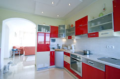 Red kitchen. Elegant kitchen in a modern house, red furniture. TV room in the background Stock Image