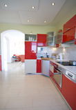 Red kitchen. Elegant kitchen in a modern house, red furniture. TV room in the background Royalty Free Stock Image