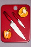 Red Kitchen Knives on Red Cutting Board with Peppers Stock Images