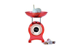 Red kitchen scales and garlic Stock Images