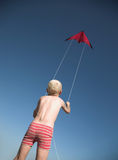 Red kite, blue sky, blonde young boy Stock Photo