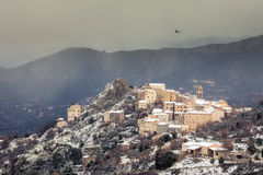 Red Kite soaring over mountain village of Speloncato in Corsica Royalty Free Stock Photography