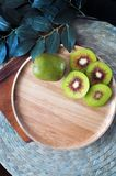 Red Kiwifruit on Wooden Plate with Copyspace. Top view of red kiwifruit on wooden plate with space for text royalty free stock photos