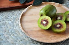 Red Kiwifruit on Wooden Plate. Pieces of red kiwifruit on wooden plate with space for text stock photography