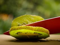 A red knife cutting a kiwi fruit over a Wood table with blurred background stock photo
