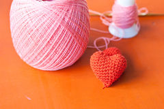 Red knit heart. The heart knit with red yarn on orange table Stock Photo