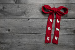 Red knitted bow with deers on wooden background for christmas Royalty Free Stock Photo