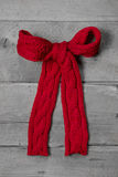Red knitted bow for a present on grey wooden background - greeti Stock Image