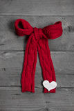 Red knitted bow with white heart on wooden background for christ Royalty Free Stock Image