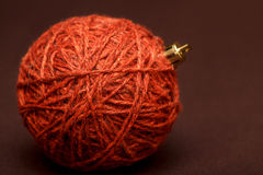 Red knitted christmas ball on brown background, close up Stock Photography