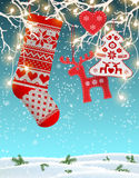 Red knitted christmas stocking with some scandinavian traditional decorations hanging on branches,  decorative electric Stock Image