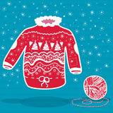 Red knitted christmas sweater and a ball of yarn. On blue background Stock Photos