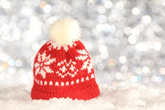 Red knitted hat. Red and white knitted hat on snow Stock Images