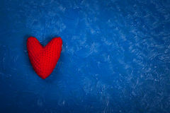 Red knitted heart on a blue background Royalty Free Stock Images
