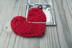 The red knitted heart is clutched by a mousetrap. The concept of fatal love. Difficult personal relationships Royalty Free Stock Photo