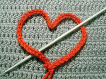 Red knitted heart on grey background Royalty Free Stock Photo