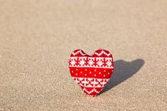 Red knitted heart on sea sand Royalty Free Stock Photo