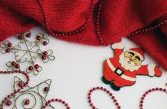 Red knitted piece on a light background with beads of red color. Nearby lies the figure of Santa Claus stock images