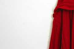 Red knitted sweater hanging on a white wall Stock Photo