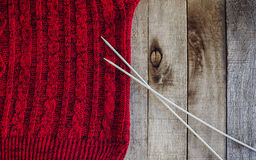 Red knitted sweater with needles texture. Beautiful red knitted sweater with needles  on wooden background. Knitting texture. Knitting pattern. Copy space. Half Stock Photo