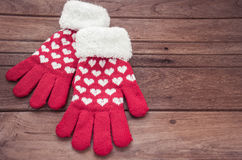 Red knitted winter gloves on wooden surface Stock Photos