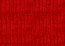 Red knitted woolen christmas background. The atmosphere of a warm sweater. New year wallpaper. Texture of the wool or acrylic knit