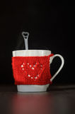 Red Knitted woolen cup with heart pattern Royalty Free Stock Photo