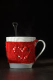 Red Knitted woolen cup with heart pattern Stock Images