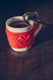 Red Knitted woolen cup with heart pattern Royalty Free Stock Images