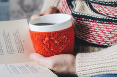 Red Knitted woolen cup with heart pattern in female hands. Book and cup of hot drink in female hands. Hands holding a cozy Mug in red knitted mitten with hot Stock Photo