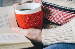 Red Knitted woolen cup with heart pattern in female hands. Royalty Free Stock Images
