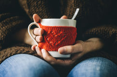 Red Knitted woolen cup with heart pattern in female hands. Hands holding a cozy Mug in red knitted mitten with hot cocoa, tea or coffee. Valentines day concept Stock Images