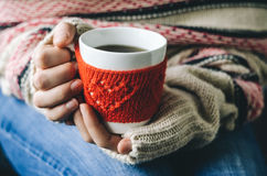 Red Knitted woolen cup with heart pattern in female hands. Royalty Free Stock Photo