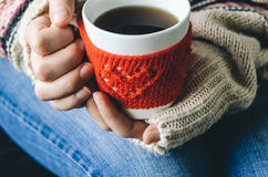 Red Knitted woolen cup with heart pattern in female hands. Stock Photography