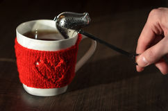 Red Knitted woolen cup with heart pattern Royalty Free Stock Image