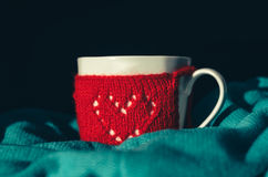Red Knitted woolen cup with heart pattern Stock Photography