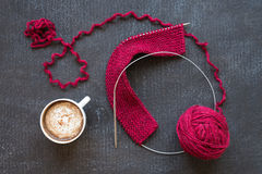 Red knitting and a cup of coffee Royalty Free Stock Images