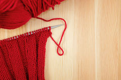 Red knitting in rib stitch with a ball of yarn Royalty Free Stock Images