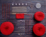 Red knitting yarn and knitting needles. Red knitting yarn, knitting needles, pins and accessories on grey-blue plate on a dark wooden background, top view Royalty Free Stock Photo