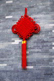 Red knot on the wall. Red Chinese knot on the old wall Stock Photo