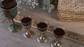 Red kosher wine four of matzah or matza Passover Haggadah. Red kosher four glasses wine with a of matzah a Passover Haggadah stock footage