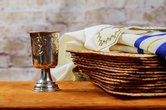 Red kosher wine with a white plate of matzah or matza and a Passover Haggadah on a vintage wood background Stock Photos