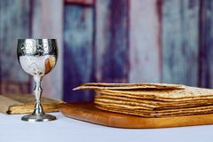 Red kosher wine with a white plate of matzah or matza and a Passover Haggadah on a vintage wood background presented as a Passover. Seder meal with copy space Royalty Free Stock Images