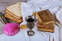 Red kosher wine with a white plate of matzah or matza and a Passover Haggadah on a vintage wood background. Presented as a Passover seder meal with copy space Stock Photo