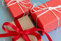 Red and kraft wrapped gift boxes on blue background close up stock photography
