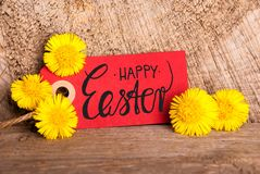 Red Label, Dandelion, English Calligraphy Happy Easter. Red Label With English Calligraphy Happy Easter. Dandelion Blossom On Wooden Rustic Background royalty free stock photos