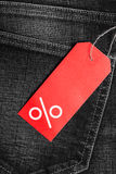 Red label with percent sign on denim Stock Images