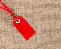 Red label with ribbon on burlap Royalty Free Stock Image
