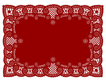 Red Lace Doily Place Mat. Vintage lace doily place mat, antique filigree pattern, red rectangle on white background for setting table, Christmas, Valentine's Day Stock Photos